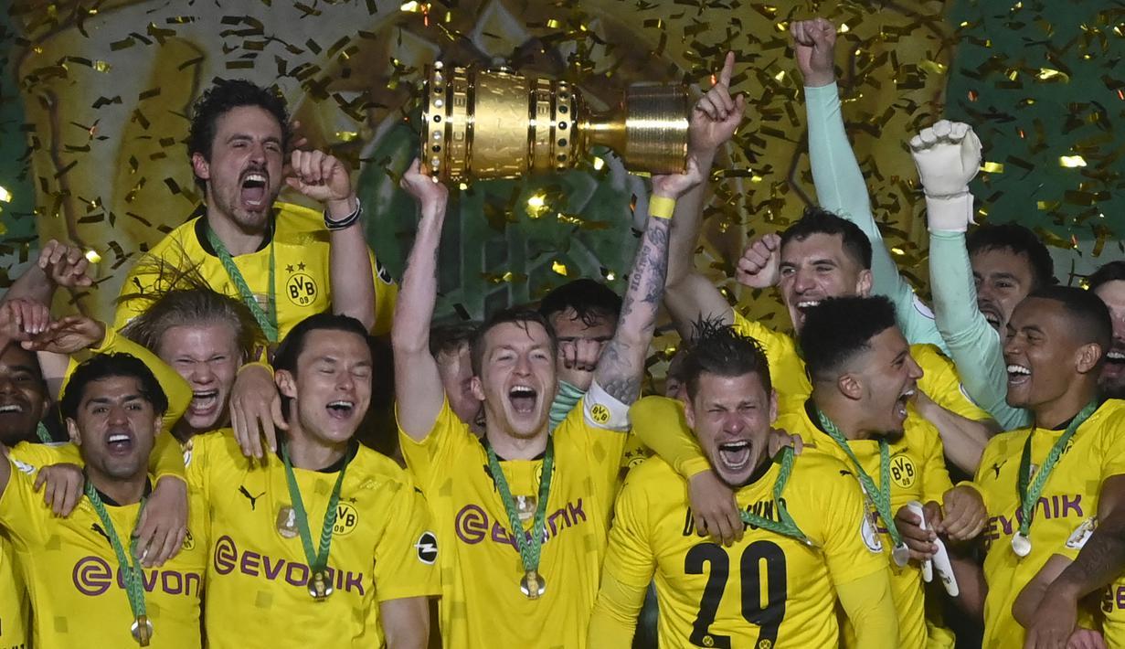 Striker dan kapten Borussia Dortmund, Marco Reus (tengah) mengangkat trofi DFB Pokal di tengah-tengah rekan setim usai kemenangan 4-1 atas RB Leipzig dalam partai Final DFB Pokal 2020/2021 di Olympiastadion, Berlin, Kamis (13/5/2021). (AFP/John MacDougall/Pool)