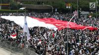 Peserta aksi massa Gerakan Nasional Kedaulatan Rakyat mengibarkan bendera Merah Putih raksasa saat melakukan unjuk rasa di perempatan dekat Gedung Bawaslu, Jakarta, Rabu (22/5/2019). Dalam aksinya, mereka meminta Bawaslu memeriksa kembali hasil Pemilu 2019. (Liputan6.com/Helmi Fithriansyah)