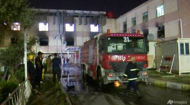 Dalam gambar yang dibuat dari video ini, responden pertama bekerja di lokasi kebakaran rumah sakit di Baghdad pada 24 April 2021. (Foto: AP)