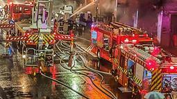 Petugas pemadam kebakaran memadamkan api di sebuah gedung di Kaohsiung, Taiwan selatan, Kamis (14/10/2021). Pemadam kebakaran mengatakan kepada BBC bahwa 79 orang telah dibawa ke rumah sakit, termasuk 14 di antaranya dalam kondisi serius. (EBC via AP )