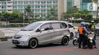 Petugas Dishub mengimbau pengguna kendaraan saat melakukan Pengawasan Pelaksanaan PSBB di Bundaran HI, Jakarta, Senin (13/4/2020). Dalam pengawasan tersebut petugas mengimbau masyarakat untuk menggunakan masker saat berpergian. (Liputan6.com/Faizal Fanani)