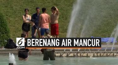 Gelombang panas yang melanda Paris membuat warga dan para turis memenuhi air mancur Trocadero. Mereka berupaya mendinginkan tubuh mereka dengan cara berenang di air mancur tersebut.