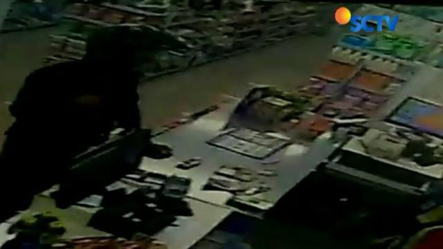 Dalam rekaman kamera CCTV ini seorang perampok dengan senjata laras panjang di punggungnya meminta sejumlah uang dan kunci brankas mini market.