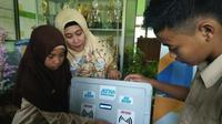 Dicky dan Haya, siswa MTSN 8 Sragen Kalijambe Sragen didampingi Kepala Sekolah Muawanatul Badriyah memeragakan cara kerja ATM Pembagi Sembako. (Foto: Liputan6.com/joglosemarnews.com/Wardoyo)