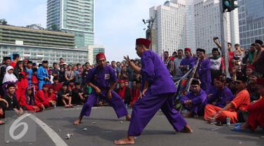 Para pendekar Betawi menunjukan aksi beladiri khas Betawi di Jakarta, Minggu (7/8). Sekitar 1000 pendekar memadati Bundaran HI untuk merayakan Lebaran Pendekar Betawi 2016. (Liputan6.com/Angga Yuniar)