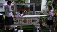 "Seorang siswa remaja mencoba masuk ke dalam peti mati di Kid Mai Death Awareness Cafe, Thailand (30/3). Selain itu cafe ini juga menyediakan menu yang cukup aneh seperti minuman rasa ""kematian"" dan ""menyakitkan"". (AFP/Lillian Suwanrumpha)"