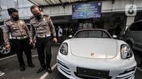 Dirlantas Polda Metro Jaya Kombes Pol Sambodo Purnomo meninjau mobil Porsche saat disita di Kantor Ditlantas Polda Metro Jaya, Jakarta, Senin (26/4/2021). (merdeka.com/Iqbal S. Nugroho)