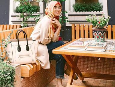 Wanita kelahiran 23 April 1994 ini selalu tampil dengan outfit yang simple salah satunya saat ia memakai hijab berwarna oranye dengan corak merah dipadu atasan berwarna krem dan celana jeans. (Liputan6.com/IG/@citraciki)