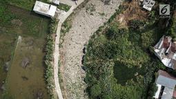 Pantauan dari udara, sampah yang menutupi Kali Pisang Batu, Tarumajaya, Kabupaten Bekasi, Rabu (9/1). Memasuki hari keempat dua alat berat dan puluhan truk dikerahkan untuk mengeruk sampah sekitar 300 ton yang sudah diangkut. (Liputan6.com/Fery Pradolo)