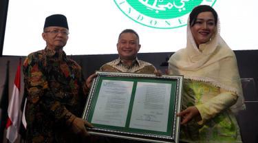 Dirut PT Kustodian Sentral Efek Indonesia (KSEI), Friderica Widyasari Dewi menerima salinan fatwa secara simbolis dari Sekretaris DSN-MUI, Anwar Abbas di Gedung BEI, Senin (1/4). KSEI secara resmi memperoleh fatwa dari DSN-MUI terkait Proses Bisnis Atas Layanan Jasa (Liputan6.com/Johan Tallo)