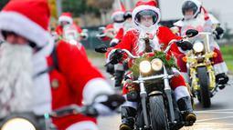Pengendara motor besar berpakaian seperti Sinterklas menyusuri jalanan selama acara amal di Lustadt, Jerman, Kamis (6/12). Mereka mengumpulkan sumbangan untuk rumah sakit Sterntaler di Speyer, yang merawat anak-anak penderita kanker. (Uwe Anspach/dpa/AFP)