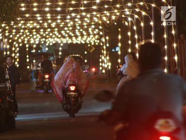 Pengendara sepeda motor melewati lampu minyak saat perayaan tumbilotohe atau penyalaan berjuta lampu minyak di akhir Ramadan di Kota Gorontalo, Jumat (31/5/2019). Tradisi ini diselenggarakan jelang Hari Raya Idul Fitri. (Liputan6.com/Arfandi Ibrahim)