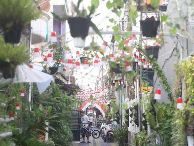 Suasana salah satu gang kampung hijau di kawasan Malakasari, Duren Sawit, Jakarta, Sabtu (15/9). Tingginya kesadaran masyarakat akan pentingnya tumbuhan membuat kawasan tersebut terlihat asri dan dipenuhi berbagai tanaman. (Liputan6.com/Immanuel Antonius)
