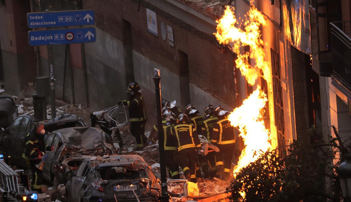 Petugas pemadam kebakaran membawa mayat di samping bangunan yang rusak di Jalan Toledo menyusul ledakan di pusat kota Madrid, Spanyol, Rabu (20/1/2021). Ledakan dahsyat yang disebabkan kebocoran gas telah menghancurkan bangunan di jantung ibu kota Spanyol, Madrid. (AP Photo/Manu Fernandez)