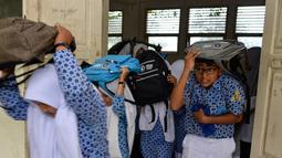 Sejumlah siswa berlarian menyelamatkan diri saat simulasi bencana gempa dan tsunami di sebuah sekolah di Banda Aceh, Aceh, Rabu (9/10/2019). Para siswa dibekali wawasan tanggap darurat bencana dan pemberian pertolongan pertama pada korban gempa. (Photo by CHAIDEER MAHYUDDIN / AFP)