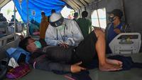 Seorang pria yang terluka dalam gempa dengan magnitudo 6,2 menerima perawatan di tempat penampungan sementara di luar Rumah Sakit Regional Sulbar, Mamuju, Sulawesi Barat, Minggu (17/1/2021). Mereka dirawat di dalam tenda darurat untuk mengantisipasi gempa susulan. (ADEK BERRY/AFP)