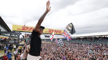 Pembalap Formula 1, Lewis Hamilton merayakan kemenangan bersama pengemarnya usai berlaga di Grand Prix Formula 1 Silverstone di Inggris, (5/7/2015). Hamilton berhasil finish di urutan pertama dengan waktu 1 jam 31 menit 27,729 detik. (Reuters/Hoch Zwei)