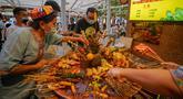 Para pengunjung memilih kudapan pedas di jalan camilan Grand Bazaar di Urumqi, ibu kota Daerah Otonom Uighur Xinjiang, China barat laut, pada 4 Juli 2020. (Xinhua/Zhao Ge)