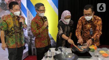 Dirut Bank BTN Haru Koesmahargyo (kanan) memasak menggunakan kompor induksi dalam acara Ayo Investasi Properti di Kawasan Transit Oriented Development (TOD) dan Launching KPR/KPA Platinum Bundling Kompor Induksi Bersama Bank BTN di Jakarta, Rabu (28/4/2021). (Liputan6.com/Pool/BTN)