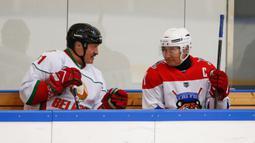 Presiden Rusia Vladimir Putin (kanan) dan Presiden Belarusia Alexander Lukashenko berbincang saat mengikuti Night Hockey League di Sochi, Rusia, Jumat (7/2/2020). Putin dan Lukashenko bermain hoki bersama saat jeda pembicaraan ekonomi antara kedua negara. (AP Photo/Alexander Zemlianichenko, Pool)