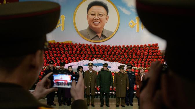 Tentara dari Rusia, Iran dan China dan Korea Utara berpose di depan pajangan selama pameran bunga 'Kimjongilia' di Pyongyang, Kamis (14/2). Korea Utara menggelar festival bunga merayakan ulang tahun mendiang ayah Kim Jong-un, Kim Jong-il.. (Ed JONES/AFP)