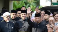 Muhyiddin Yassin (kedua kanan) melambaikan tangan sebelum upacara pelantikannya sebagai Perdana Menteri Malaysia di Istana Negara, Kuala Lumpur, Minggu (1/3/2020). Pelantikan dilakukan dengan alasan kursi kepemimpinan harus segera terisi. (NAZRI RAPAAI/AFP/MALAYSIA'S DEPARTMENT OF INFORMATION)