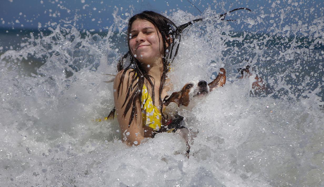 Mariana Rojas dan anjingnya bermain ombak di lepas pantai Los Angeles setelah dibuka kembali di La Guaira, Venezuela, Jumat (23/10/2020). Pemberlakuan lockdown yang ketat akibat COVID-19 memaksa penutupan pantai di seluruh negeri pada Maret lalu dan dibuka kembali minggu ini. (AP/Matias Delacroix)