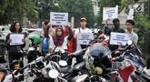 Koalisi Pejalan Kaki membawa poster saat menggelar aksi Tamasya Trotoar Kita di lokasi parkir liar sepanjang jalur pedestrian Gelora Bung Karno (GBK), Jakarta, Minggu (9/12). (Merdeka.com/Iqbal S. Nugroho)