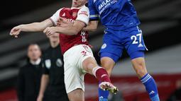 Bek Leicester City, Timothy Castagne berebut bola udara dengan bek Arsenal, Kieran Tierney  pada pertandingan lanjutan Liga Inggris di Stadion Emirates di London, Inggris, Minggu (25/10/2020). Leicester City menang 1-0 atas Arsenal. (Will Oliver/Pool via AP)