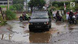 Kendaraan menghindari kubangan pada jalan yang rusak di Jalan Pertamina, Kemiri Muka, Depok, Jawa Barat, Selasa (5/3). Kondisi tersebut mengganggu aktivitas warga serta pengguna jalan. (Liputan6.com/Immanuel Antonius)
