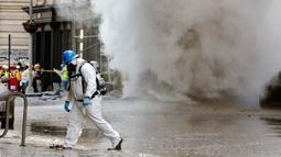 Kepulan asap putih mengepul ke udara setelah sebuah pipa uap meledak di Distrik Flatiron, Manhattan, Kamis (19/7). Tidak ada korban luka setelah ledakan pipa uap besar yang menutup jalan-jalan dan evakuasi paksa tersebut. (AP Photo/Richard Drew)