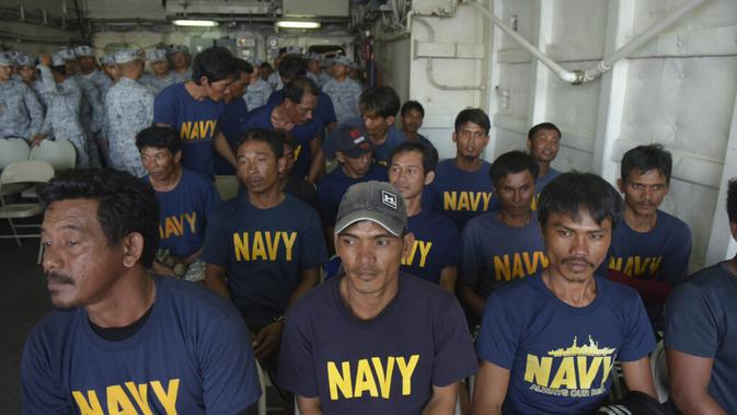 Nelayan Filipina di kapal AL Filipinia usai diselematkan dari kapal mereka yang tenggalam di Laut China Selatan. Diduga kapal nelayan itu ditabrak-lari oleh kapal Tiongkok. Beijing turut mengutuk insiden itu. (AP PHOTO)