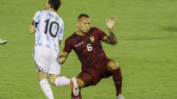 Lionel Messi mendapatkan tekel keras dari bek Venezuela, Luis Martinez. Martinez mengangkat kaki terlalu tinggi saat mencoba merebut bola dari kaki La Pulga.  (Foto: AFP/Miguel Gutierrez, Pool)