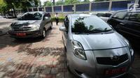 Petugas keamanan mengecek mobil operasional KPK yang akan dilelang di Gedung KPK Lama, Jakarta, Selasa (27/2). KPK akan melelang kendaraan operasional inventaris yang telah berumur di atas 10 tahun. (Liputan6.com/Helmi Fithriansyah)