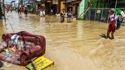 Sejumlah warga melintasi banjir yang merendam komplek Pondok Gede Permai, Jatiasih, Bekasi, Jumat (22/4). Banjir yang sempat mencapai 4 meter di perumahan tersebut merendam lebih dari 500 rumah yang dihuni ribuan warga. (Liputan6.com/Fery Pradolo)