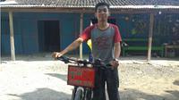 Sandi Setiawan di depan rumahnya dengan sepeda yang ia gunakan mudik. (KRJogja.com/Fatimah Arum)