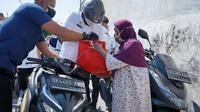 Wali Kota Medan, Bobby Nasution, berkeliling mengendarai motor matik dengan membawa sejumlah paket sembako