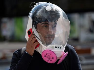 Perancang industri Kolombia Ricardo Conde menggunakan ponsel saat memakai masker baru dengan ventilasi demi mencegah penyebaran Virus Corona COVID-19, dirancang olehnya bersama seorang dokter medis dan dua insinyur aeronautika di Bogota, Kolombia pada 30 Juli 2020. (Juan BARRETO / AFP)