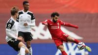 Gelandang Liverpool, Mohamed Salah (kanan) melepaskan tendangan yang masih melenceng dari gawang Fulham dalam laga lanjutan Liga Inggris 2020/21 di Anfield Stadium, Minggu (7/3/2021). Liverpool kalah 0-1 dari Fulham. (AFP/Clive Brunskill/Pool)