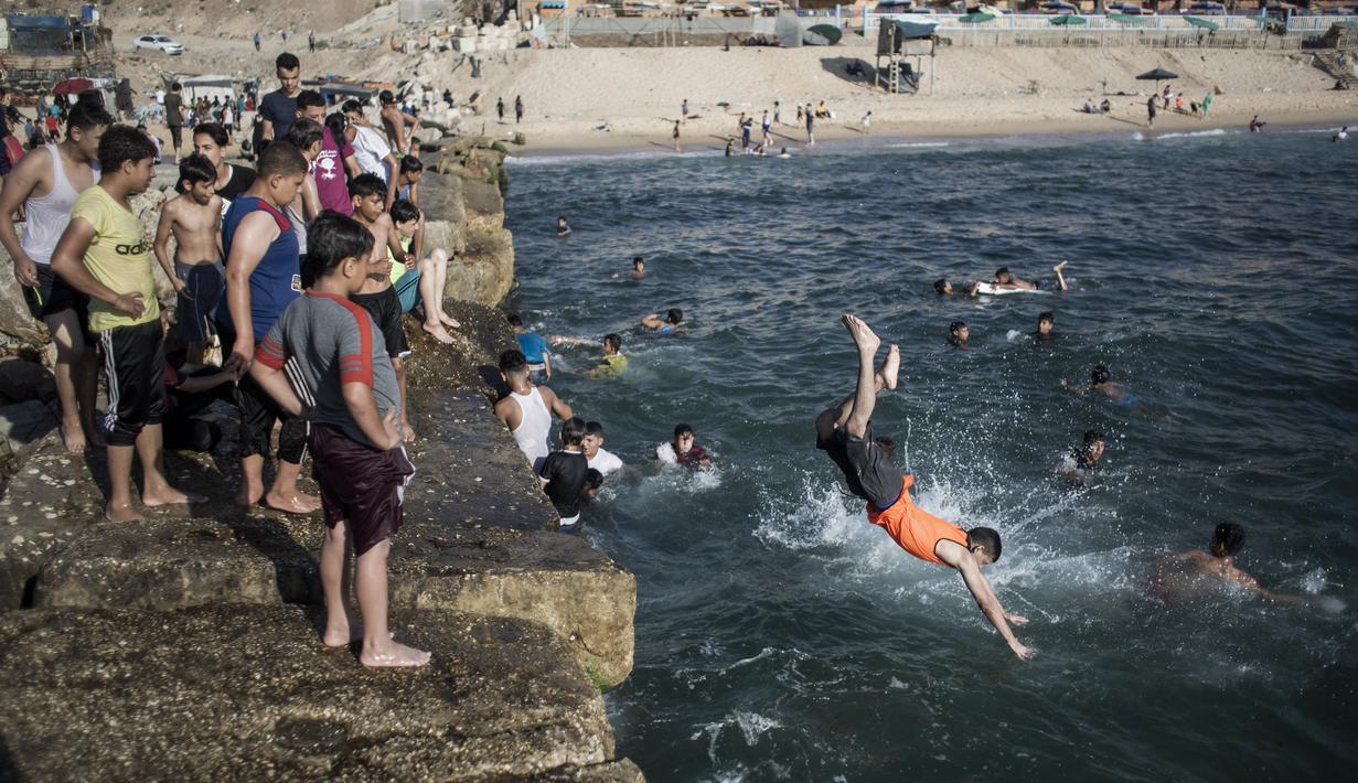 Warga melompat ke laut saat menikmati musim panas yang cerah di pantai Kota Gaza, Palestina, Jumat (3/7/2020). (AP Photo/Khalil Hamra)