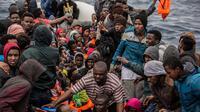 Pengungsi dan migran menunggu untuk diselamatkan oleh LSM Spanyol Proactiva Open Arms di atas sebuah kapal karet, 60 mil sebelah utara Al -Khum, Libya (18/2). Para pengungsi dan migran ini meninggalkan Libya untuk ke Eropa. (AP Photo/Olmo Calvo)